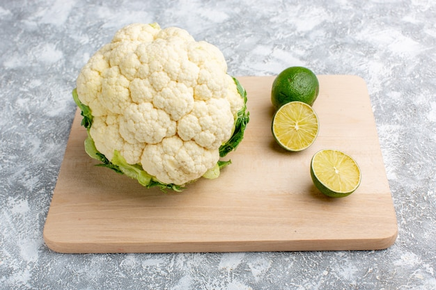 Front view of fresh cauliflower with lemon on the wooden rustic grey desk