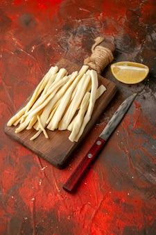 暗い食事スナックの写真の色の木製の机の上でスライスした正面のフレッシュ チーズ