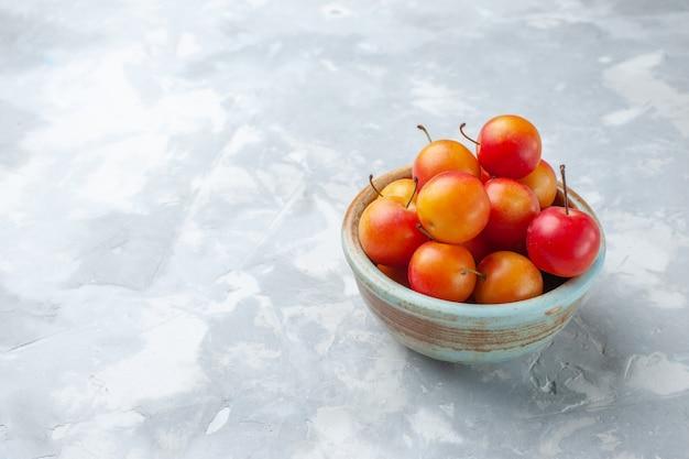 Вид спереди свежие сливы кислые и свежие внутри кастрюли на светлом столе фрукты кислые свежие спелые