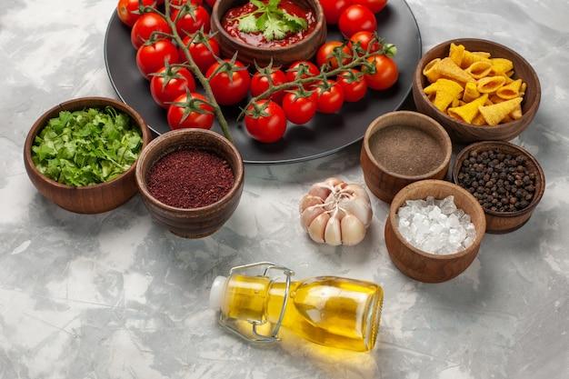 Свежие помидоры черри, вид спереди, внутри тарелки с зеленью и разными приправами на белой поверхности, овощная еда, здоровый салат