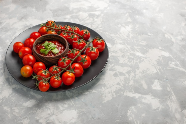 Front view fresh cherry tomatoes inside plate with tomato sauce on the white surface vegetable meal food health salad