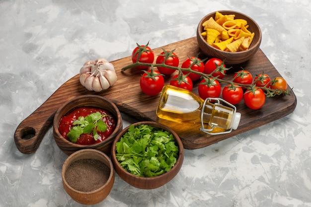Свежие помидоры черри с приправами и зеленью на белой поверхности, вид спереди, здоровый салат