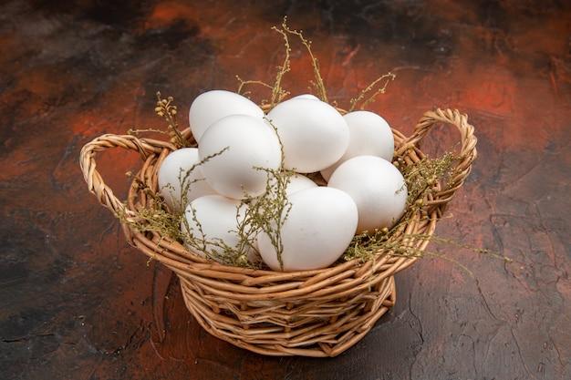 Vista frontale uova di gallina fresche all'interno del cesto sulla superficie scura