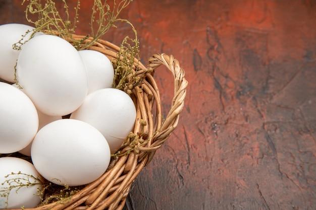 어두운 표면에 바구니 안에 전면보기 신선한 닭고기 달걀
