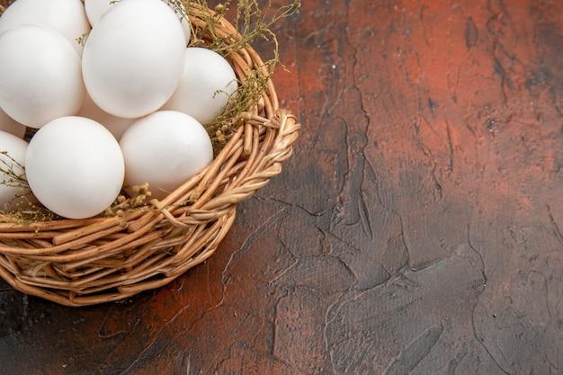 Свежие куриные яйца, вид спереди, внутри корзины на темной поверхности