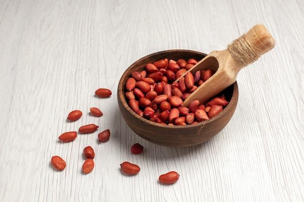 Vista frontale di arachidi fresche e pulite all'interno del piatto sul dado della scrivania bianco molti snack di conchiglie di piante di alberi