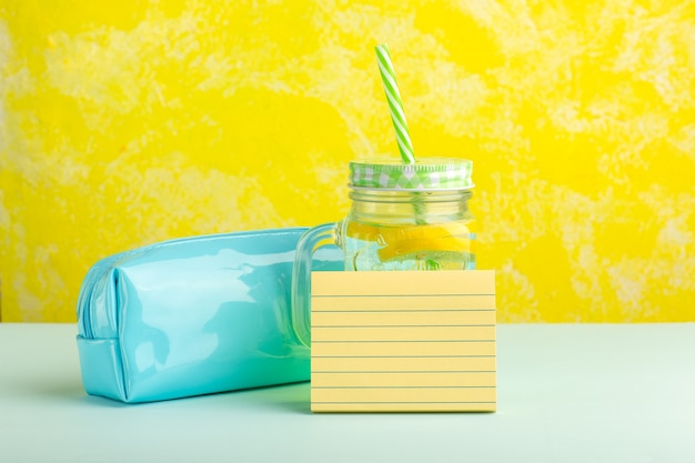 黄色の表面にペンボックスと正面図の新鮮なカクテル