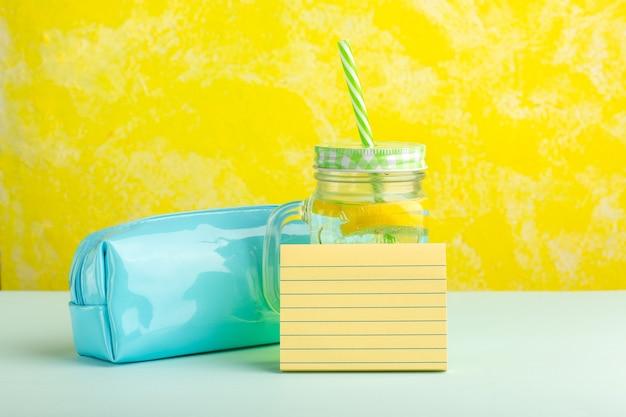 Cocktail fresco di vista frontale con la scatola della penna sulla superficie gialla