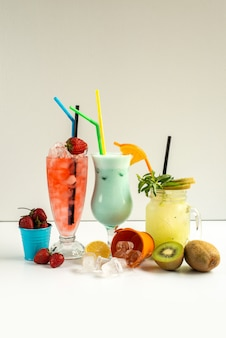 A front view fresh cold cocktails inside glasses with straws along with fresh fruits isolated on white