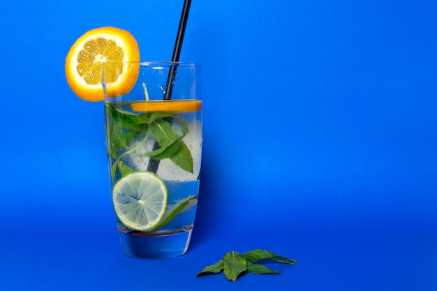 A front view fresh cold coktail with ice-cubes leaves citruses and black straw inside glass on blue