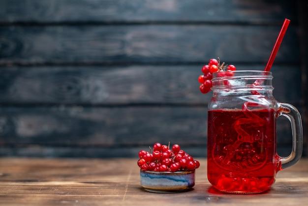 正面から見た新鮮なクランベリー ジュースは、暗い机のバーのフルーツ写真カクテル カラー ドリンク ベリーの缶