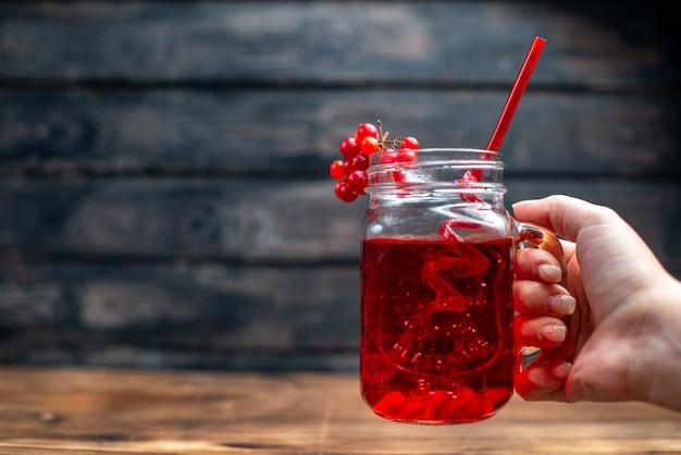 Вид спереди свежий клюквенный сок внутри банка с соломкой на темном баре фруктовый коктейль цветной напиток ягода