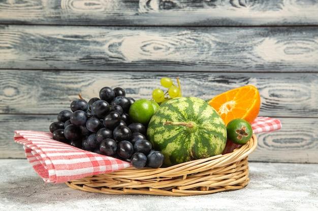 Вид спереди свежий темный виноград с апельсином и арбузом на белом фоне спелые фрукты мягкие витаминное дерево свежие