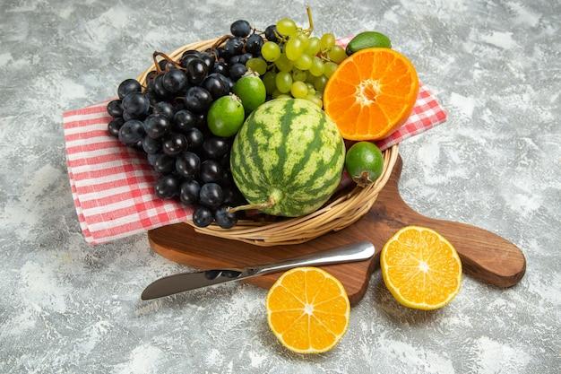 Вид спереди свежий темный виноград с апельсином и арбузом на белом фоне спелые фрукты спелые витаминное дерево свежие