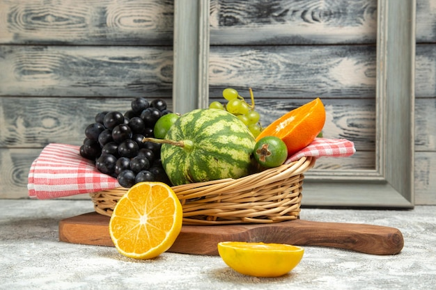 Vista frontale fresca uva scura con arancia e anguria su sfondo bianco frutta matura dolce vitamina albero fresco
