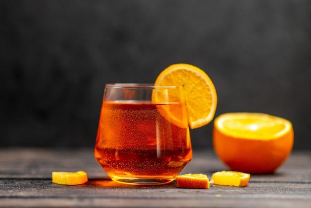 Vista frontale del delizioso succo fresco in un bicchiere con lime arancioni su sfondo scuro