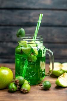 正面から見た新鮮なフェイジョア ジュースは、暗いバーのフルーツ カラー写真カクテルに青リンゴが入った缶の中にあります