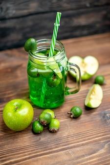 正面から見た新鮮なフェイジョア ジュースは、暗いバーに緑のリンゴが入った缶の中に入っています。