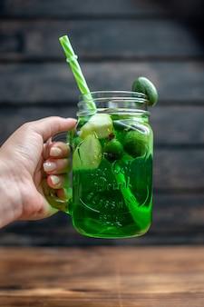 正面から見た新鮮なフェイジョア ジュースは、暗いバーにストローが入った缶に入っています。