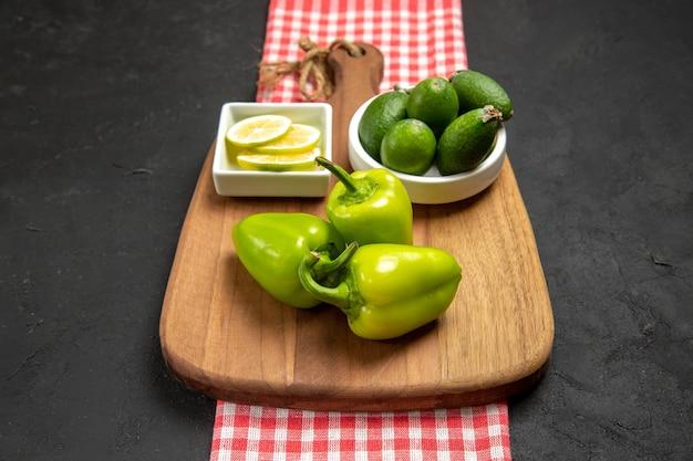 暗い表面のフルーツ柑橘類の植物の食事に緑のピーマンとレモンの正面図新鮮なフェイジョア