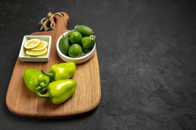暗い表面のフルーツ健康柑橘類の食事植物に緑のピーマンとレモンと正面図新鮮なフェイジョア