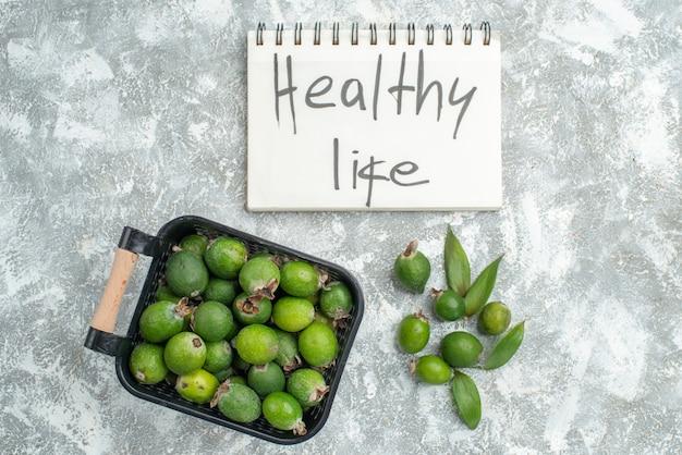 Вид спереди свежие фейхоа в корзине здорового образа жизни, написанные в блокноте на серой поверхности