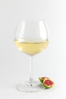 正面図新鮮なイチジクのスライスと白い机の上のワイングラスフルーツ新鮮なビタミンの木の植物写真アルコールバー 無料写真