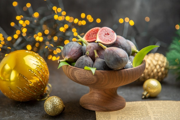 Vista frontale di fichi freschi intorno ai giocattoli di natale sulla foto di natale di gusto scuro di frutta da scrivania scura