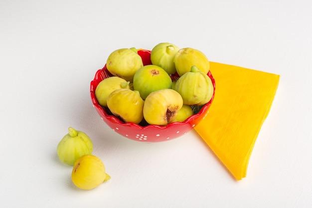 Vista frontale fichi freschi dolci e deliziosi feti all'interno del piatto sulla superficie bianca