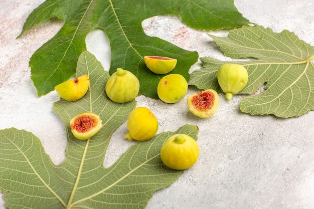 Front view fresh figs sweet fetuses with leaves on the light white surface