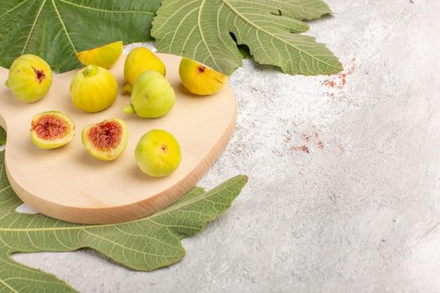 Vista frontale fichi freschi feti dolci con foglie sulla scrivania bianca