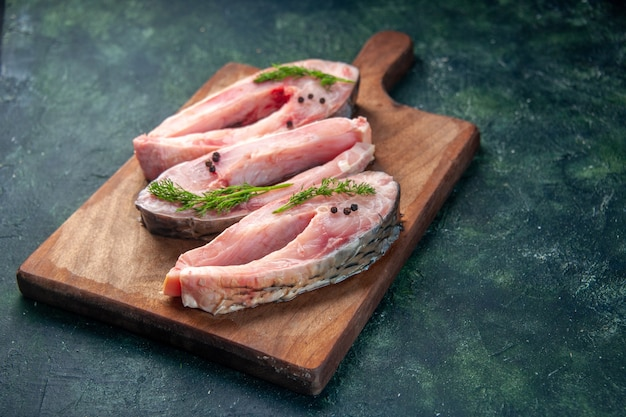 Vista frontale fette di pesce fresco sulla superficie blu scuro cibo salute pepe colore pasto insalata dieta frutti di mare oceano acqua pesce