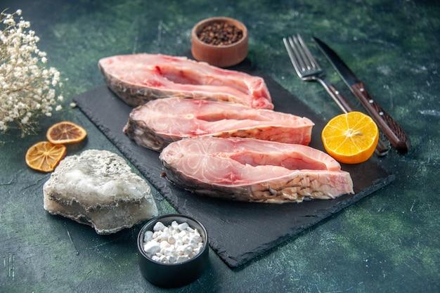 Vista frontale fette di pesce fresco sulla superficie scura foto di acqua grezza frutti di mare carne colore cena oceano pasto