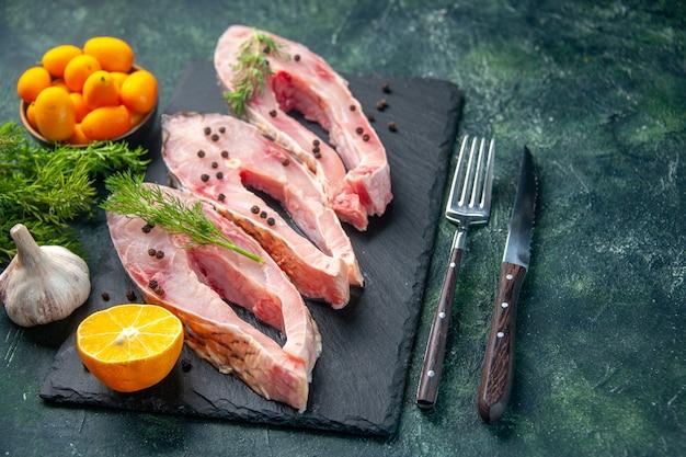 Vista frontale fette di pesce fresco con verdure e kumquat sulla superficie scura carne dell'oceano pasto crudo foto di acqua pesce colore cena