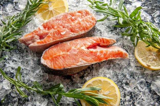 Vista frontale fette di pesce fresco con limone e ghiaccio su piatto di colore scuro carne cibo oscurità foto frutti di mare
