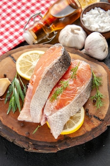 Vista frontale fette di pesce fresco con fette di limone aglio e condimenti su pesce scuro colore piatto carne foto crudo