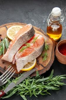 Vista frontale fette di pesce fresco con fette di limone e condimenti su pesce scuro colore piatto carne foto crudo