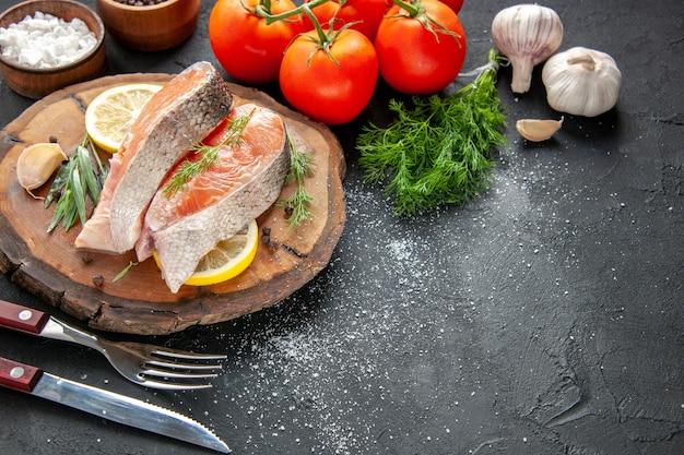 Vista frontale fette di pesce fresco con fette di limone e pomodori su carne di colore scuro piatto di pesce foto cibo crudo