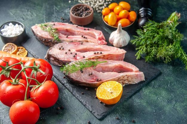 Вид спереди кусочки свежей рыбы с перцем зелень и овощи на темной поверхности мясо океана сырье вода фото морепродукты цвет ужин