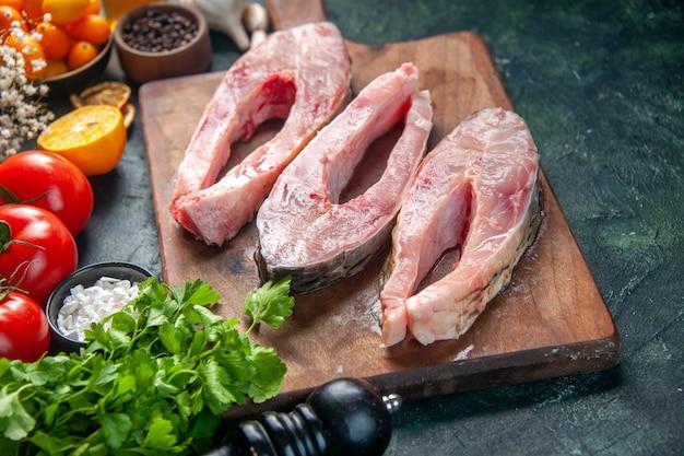 Вид спереди ломтики свежей рыбы с помидорами и зеленью на темной поверхности еда салат здоровая диета перец цветная еда