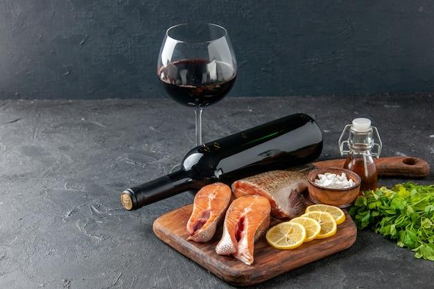 正面図新鮮な魚とレモンスライスと暗い背景のワインのボトル魚のサラダ水肉海の海の食事ディナーシーフード