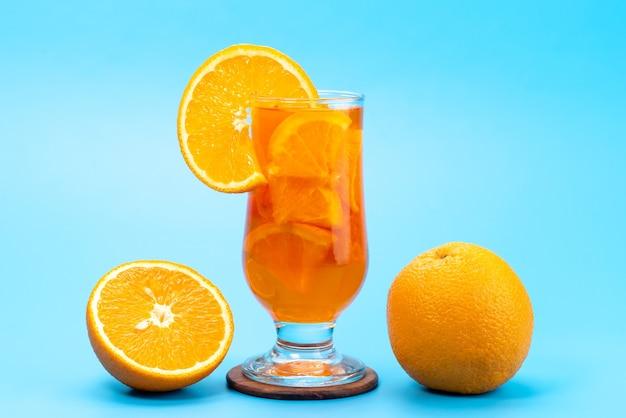 Un cocktail della frutta fresca di vista frontale con il raffreddamento del ghiaccio delle fette della frutta fresca sul blu, colore della frutta del cocktail della spremuta della bevanda
