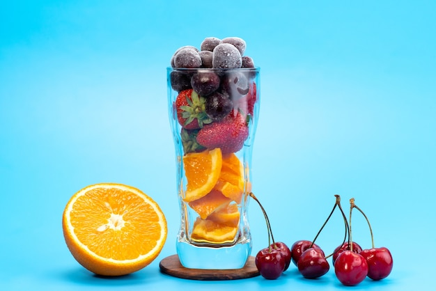 A front view fresh fruit cocktail with fresh fruit slices ice cooling on blue, drink juice cocktail fruit color