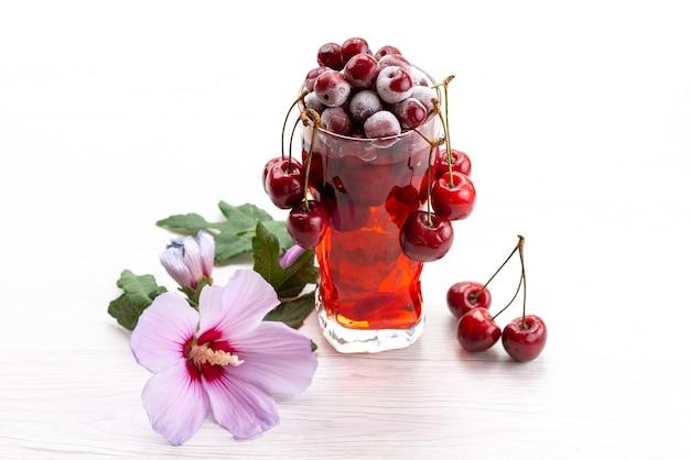 Un cocktail di frutta fresca di vista frontale con il raffreddamento del ghiaccio delle ciliege rosse fresche su bianco, colore della frutta del cocktail della spremuta della bevanda
