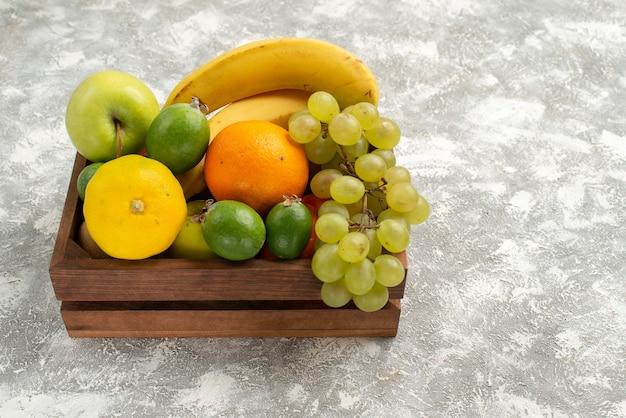 Vista frontale composizione di frutta fresca banane uva e feijoa su uno sfondo bianco frutta dolce vitamina salute fresca