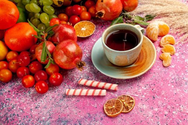 淡いピンクの机の上のお茶と正面図の新鮮な果物の組成
