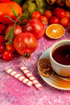 淡いピンクの表面にお茶を入れた正面図の新鮮な果物の組成物