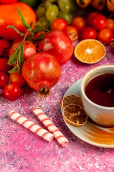 Composizione nella frutta fresca di vista frontale con una tazza di tè sulla superficie rosa-chiaro