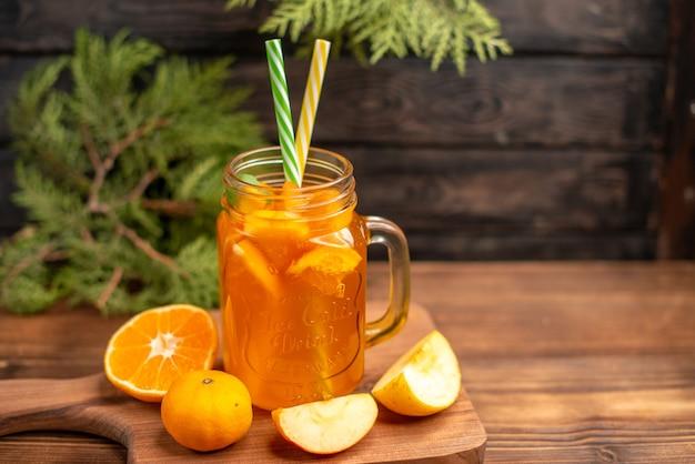 Vista frontale del succo di frutta fresca in un bicchiere servito con tubi e mela e arancia su un tagliere di legno
