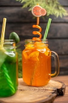 Vista frontale di succhi di frutta fresca in un bicchiere servito con tubi su un tagliere di legno su un tavolo marrone